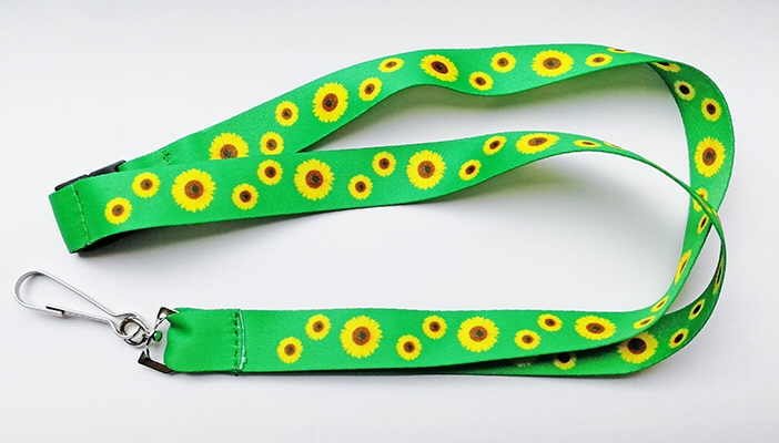 A light green lanyard with small sunflowers printed on it