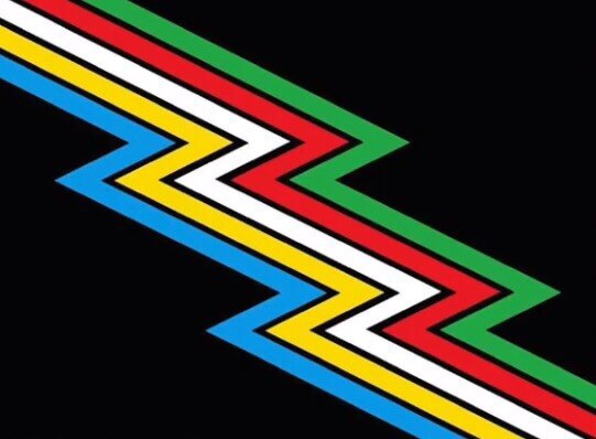 The disability pride flag a blue, yellow, white, red and green lightening bolt on a black background.